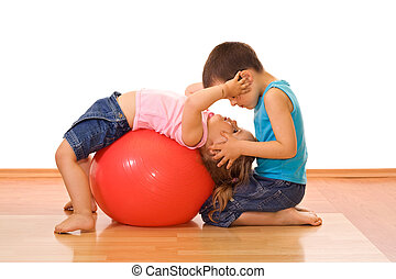 Gym kids - Two adorable kid playing with a large rubber ball...
