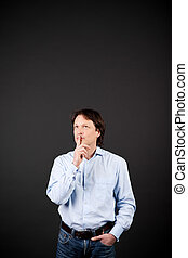 Thoughtful casual young man in jeans standing a dark studio...