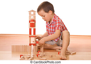 Building a wooden block castle - Little boy playing with...