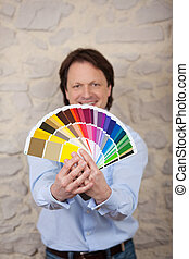 Interior designer with paint colour cards in all shades of...