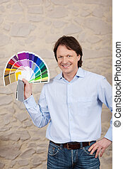 Decorator with paint sample colours - Smiling male decorator...