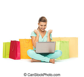 woman with laptop and shopping bags - happy young woman with...