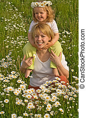 Woman and little girl on the daisy field