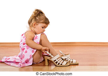 Trying mom\'s shoes - Little girl trying her mother\'s shoes...