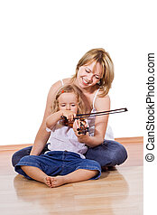 Woman teaching little girl to play the violin