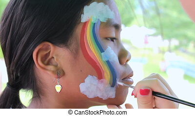 Colorful Rainbow Face Painting - A cute 11 year old Asian...
