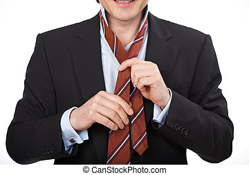 Man tying his tie - Closeup vew of the hands of a man in a...