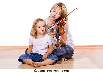 Enjoying the music - Woman and little girl enjoy playing and...