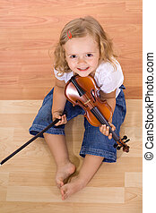 Little musician girl - Little girl sitting on the floor with...