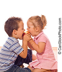 Eating an apple - Little boy and girl bite an apple