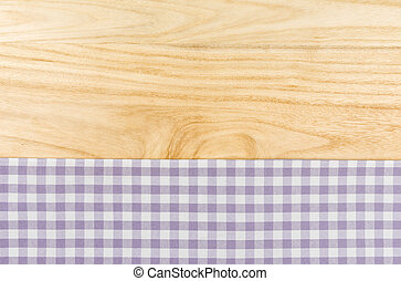 Purple checkered table cloth on a wooden background
