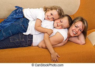 Family heap - Woman and kids playing togheter on the sofa