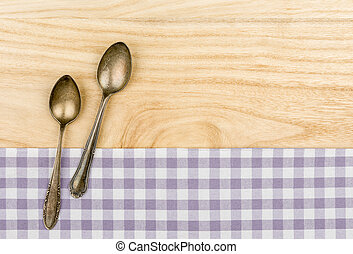 Two silver spoons on a purple checkered table cloth on a...