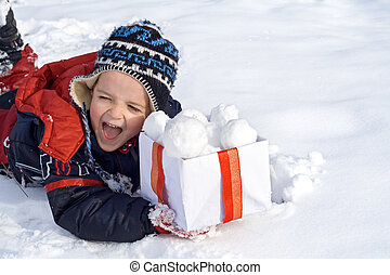 Happy boy in the snow with a box of snowballs - Happy boy...