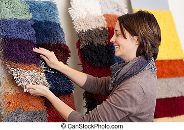 Smiling woman choosing carpet samples from a colourful...