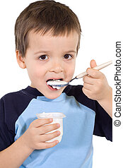 Little kid eating yoghurt with a large spoon - isolated