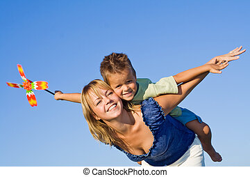 We are flying - Woman and littel boy playing aeroplane with...