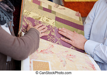 Woman looking at wallpaper and fabric swatches holding a...