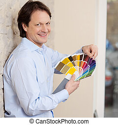 Man checking paint colours against a wall - Smiling good...