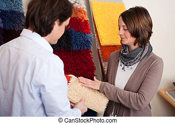 Couple choosing a carpet holding up a sample swatch in her...