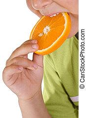 Boy eating orange slice - closeup - Closeup of boy eating...