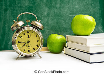 School time again Clock, apples and books on teachers table,...