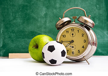 School time again. Clock, small ball and apple on teacher's...