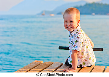 happy little boy sitting on a pier at sunset by the sea
