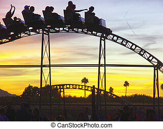 Roller coaster cresting over the top of a hill against a...