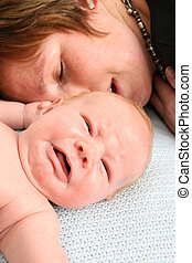 Exhausted - Tired mother and crying newborn baby, both...