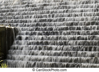 Spring Water - Water flowing down a terraced wall in...