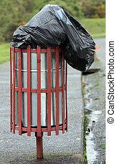 rubbish bin - a steel rubbish bin overfull with garbage on...