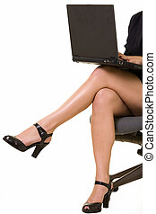 Business legs - Womans crossed legs sitting on chair working...