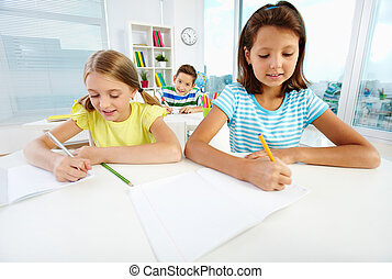 Schoolwork - Diligent pupils being busy doing their...