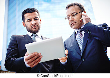 Mobile negotiations - Experienced businessmen discussing...