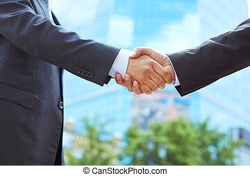 Conclusion - Business associates shaking hands beginning...