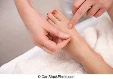 Acupuncture treatment on foot with red toenail