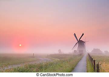 windmill and rising sun in fog - Dutch windmill and rising...