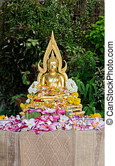 A shaded Buddha statue covered with flower petals after...