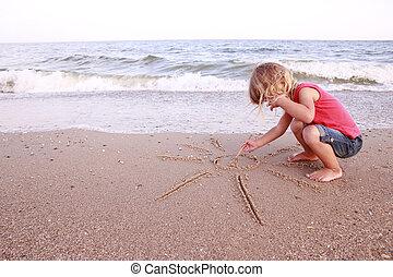 girl draws a sun in the sand on the beach - Little girl...