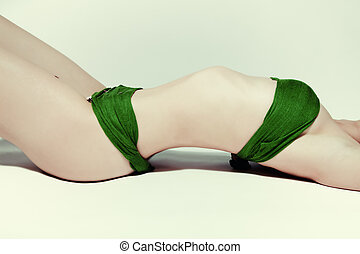 Sexy body of young woman in green bathing suit on white...