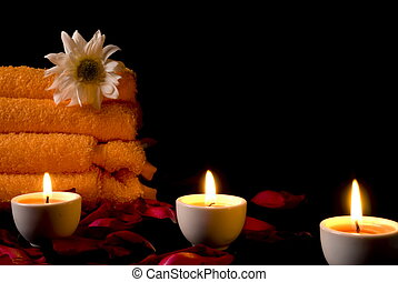 Spa Things - candles and flowers before towel at night .