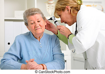 otolaryngologycal exam - doctor examining senior patients...