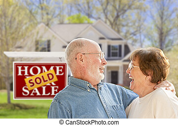 Senior Couple in Front of Sold Real Estate Sign and House -...