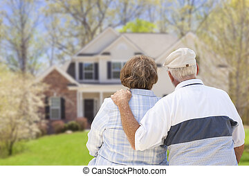 Happy Senior Couple Looking at Front of House - Happy Senior...