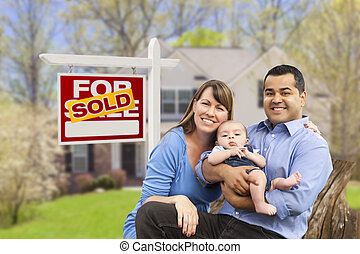 Young Family in Front of Sold Real Estate Sign and House -...