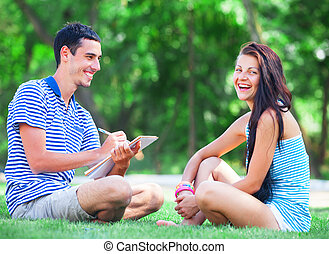 Young students sitting on green grass with note book.
