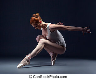 Graceful slender ballerina dancing in studio, close-up