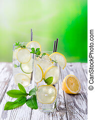 Cocktail with ice and lemon slices isolated on white...
