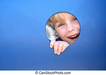 Child Peeking Through Hole at Playground